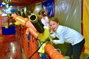 ילדה נהנת מכוונת את התותח גבוה כדי לירות