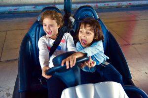 שתי בנות צועקות במכונית מתנגשת. בת אחת מנסה להסיט את ההגה כדי לא להתנגש.