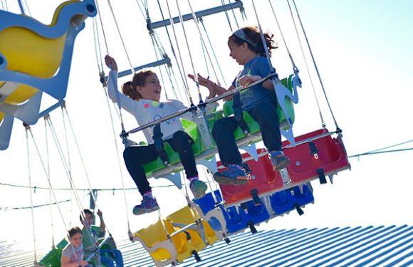 ילדות משחקות וצוחקות בקרוסלת שרשראות מסתובבת
