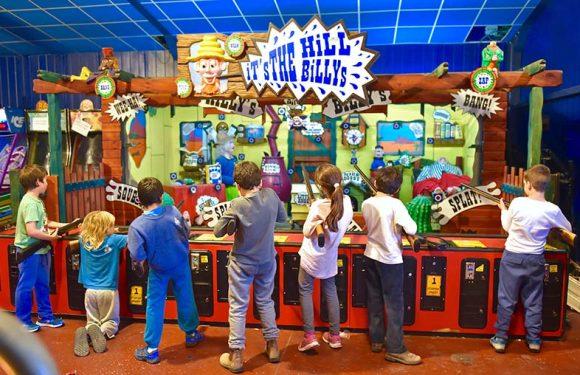 ילדים עם רובים עם הגב למצלמה, משחקים במתקן מערב הפרוע