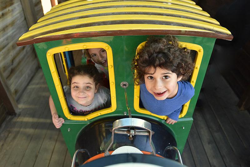 ילד מוציא חצי גוף ומסתכל למצלמה מקרון הרכבת. בחלון השני של הקרון שתי בנות מציצות עם חיוך