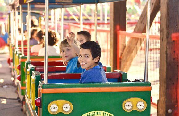 צילום מגב הרכבת, ילדים מסתכלים אחורה מחייכים ומנופפים לשלום