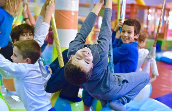 ילד תלוי הפוך על כדור במתקן רך יחד עם עוד ילדים תלויים ומחייכים
