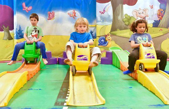 ילדה ושני ילדים במכוניות קטנות על מסלול גלי