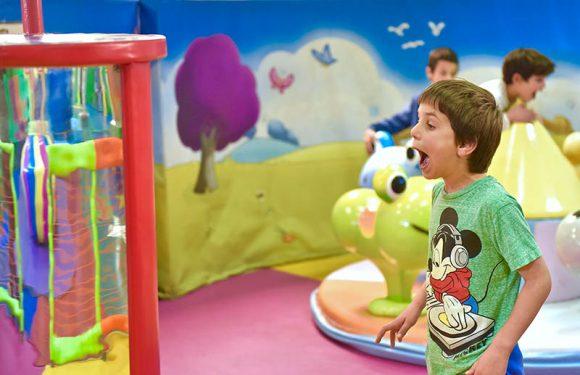 ילד עושה פרצוף מצחיק מול מראה מעוותת, ברקע ילדים קטנים על קרוסלת חיות מסתובבת