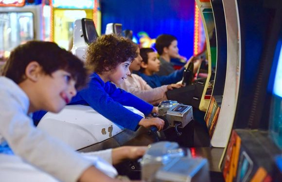 ילדים מרוכזים במשחקי וידאו של רכיבה על אופנוע ונהיגה במכונית