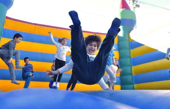 ילד קופץ בארמון מתנפח עם הלשון בחוץ. ברקע עוד יםדים נהנים קופצים.