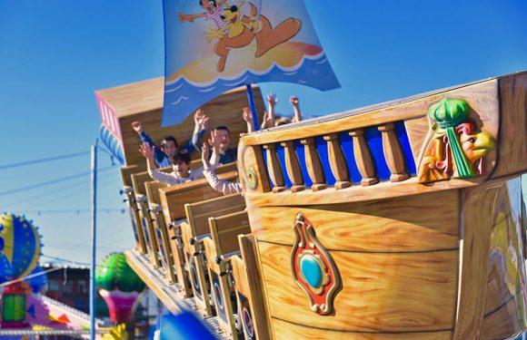 ילדים בסירה עם ידיים למעלה ברקע קרוסלת בלונים מתנפחים