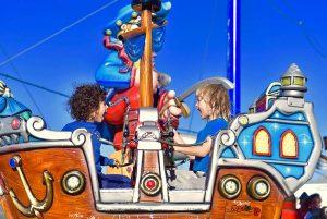 שני ילדים יושבים אחד מול השני בתא קרוסלת פיראטים וצועקים