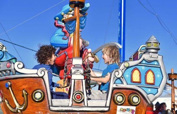 שני ילדים יושבים בתוך קרוסלת פיראטים, מסתכלים אחד על השני ופותחים את הפה כאילו צועקים