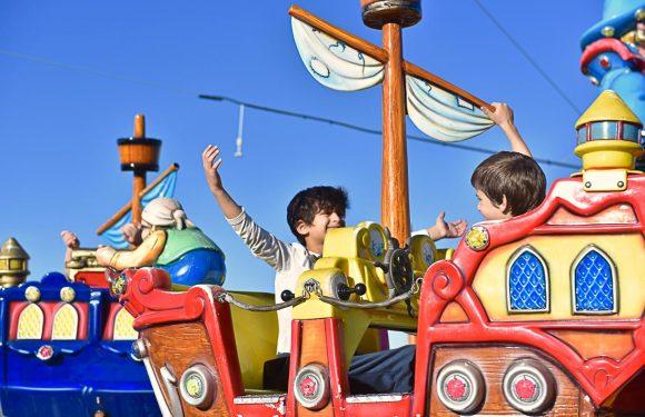 שני ילדים יושבים בתוך קרוסלת פיראטים, מסתכלים אחד על השני, מחייכים, ילד אחד מרים את ידיו באוויר