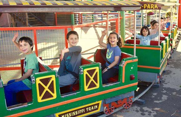 ילדים יושבים ברכבת מנופפים לשלום בזמן נסיעה