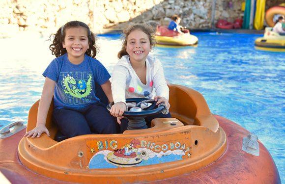 שתי ילדות בסירה מתנגשת בבריכה מחייכות למצלמה