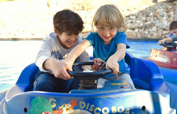 שני ילדים יושבים בתוך סירת אבוב, שניהם אוחזים בהגה הסירה, אחד מסתכל למצלמה והשני מתאמץ לסובב את ההגה